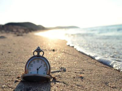 pocket-watch-half-submerged-in-the-sand-on-sunny-beach-with-sea