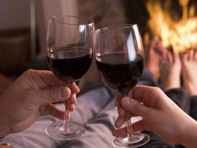 Couple In Front Of Fire With Wine